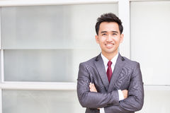 Asian businessman standing arms crossed and smiling Stock Photo