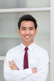 Asian businessman standing arms crossed and smiling Stock Image