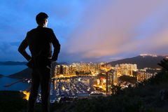Asian businessman standing in the hill. And looking at the skyscrapers and harbor in Aberdeen, Hong Kong, Asia Royalty Free Stock Image