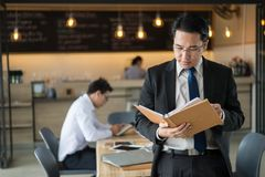 Asian businessman standing and holding document file about financial report on hand. Asian businessman in black suit, who standing and holding document file stock images