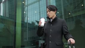 Asian businessman is standing near the airport and waiting for transfer. Young korean man in black coat is drinking coffee from the paper cup and holding the stock footage