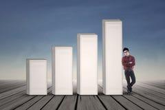 Asian businessman standing next to growing bar chart Royalty Free Stock Photos