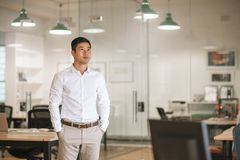 Asian businessman standing in an office thinking up new ideas Stock Images