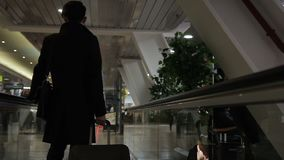 The asian businessman is standing on the speedwalk in the airport. The investor is wearing black coat and has a luggage and a bag while traveling. The man stock video footage