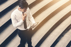 Asian businessman standing on staircase outdoor and using tablet with looking data result financial technology. royalty free stock photos