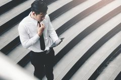 Asian businessman standing on staircase outdoor and using tablet royalty free stock image