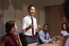 Asian businessman standing to address colleagues at meeting stock images