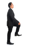 Asian businessman stepping up stair case. Full body side view of attractive young Southeast Asian businessman stepping up stair case, isolated on white Royalty Free Stock Photos
