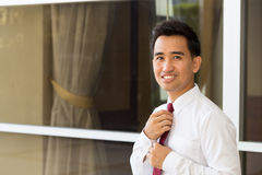Asian businessman straightening his tie Stock Images