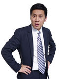 Asian businessman. Studio portrait of an angry asian businessman, arms akimbo Stock Image