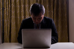 Asian businessman in suit attempting to hack computer network. In dark Stock Photography