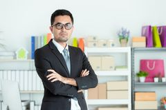Asian businessman in suit looks good standing cross his arm in front of office desk. Small Business Startup Initiative. royalty free stock photography