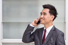 Asian businessman in suit speaking on the phone Royalty Free Stock Photos