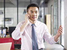 Asian businessman talking on cellphone Stock Images