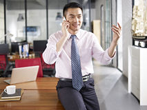 Asian businessman talking on cellphone Stock Photography