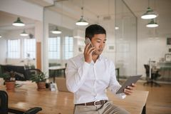Asian businessman talking on his cellphone and using a tablet Royalty Free Stock Photo