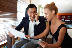 Asian businessman talking on mobile phone while his female partner using digital tablet Stock Photography