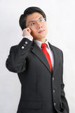 Asian businessman talking on the phone. A young Asian businessman talking on his cell phone Royalty Free Stock Image