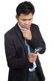Asian businessman thinking with magnifying glass Royalty Free Stock Images