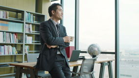 Asian businessman thinking in office stock footage