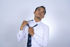 Asian businessman tired while removing the tie. Photo image of asian businessman tired while removing the tie Stock Photo