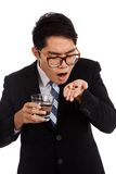 Asian businessman about to eat medicine with glass of water Stock Image