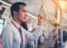 An Asian businessman is traveling a public train. An Asian businessman is traveling a public train stock photography