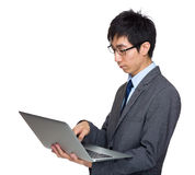 Asian businessman type on laptop computer. Isolated on white stock image