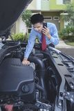 Businessman Use mobile phone asking for a help. Asian Businessman Use mobile phone asking for a help while checking out engine Stock Photos