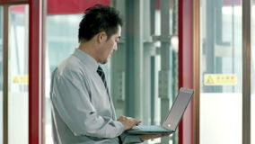 Asian businessman using laptop computer in hallway. Asian businessman using laptop computer in elevator hall in office building stock footage