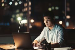 Asian businessman using a laptop at his desk at night Stock Images