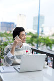 Asian businessman using mobile phone while working with laptop o Stock Images
