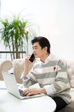 Asian businessman using mobile phone while working with laptop o Royalty Free Stock Photography