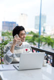 Asian businessman using mobile phone while working with laptop o Royalty Free Stock Photos