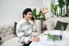 Asian businessman using mobile phone while working with laptop o Royalty Free Stock Photo