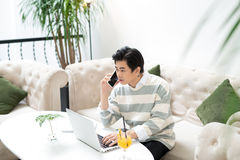 Asian businessman using mobile phone while working with laptop o Stock Photography