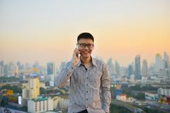 Asian businessman using phone with city  background, technology. Asian businessman using phone with city background, technology communication concept Stock Photo