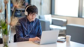 Asian businessman using smartphone in workplace. Young Asian businessman with glasses and headphones listening to music. Male entrepreneur working with laptop Stock Photos