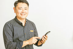 Asian businessman using a tablet pc at white background Royalty Free Stock Image