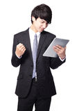 Asian businessman using touch pad with annoyed face Royalty Free Stock Image