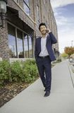 Asian Businessman walking while talking on the cell phone outside. Asian Businessman walking outside while talking on the cell phone, smiling, day time Royalty Free Stock Images