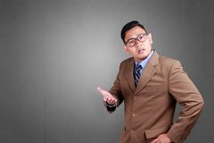 Businessman Disappointing Gesture. Asian businessman wearing suit disappointing gesture. Close up body portrait stock photography