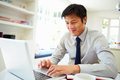 Asian Businessman Working From Home On Laptop. In Kitchen Royalty Free Stock Images