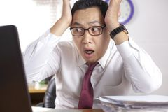 Asian Businessman Working on Laptop Shocked Stunned gesture. Portrait of Asian businessman looking at his laptop with shocked stunned worried facial expression stock photo