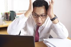 Asian Businessman Working on Laptop Shocked Stunned gesture. Portrait of Asian businessman looking at his laptop with shocked stunned worried facial expression royalty free stock photography