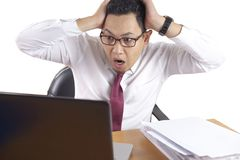 Asian Businessman Working on Laptop Shocked Stunned gesture. Portrait of Asian businessman looking at his laptop with shocked stunned worried facial expression royalty free stock photos