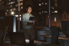 Asian businessman working late in his office with a tablet Stock Images