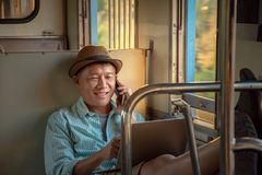 Asian businessman working online with a laptop and cellphone feel relaxed while travel by train royalty free stock images