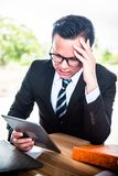 Working pressured and unsuccessful. Asian Businessman working on tablet, pressured to work and unsuccessful Stock Image