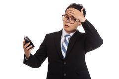 Asian businessman worry look at alarm clock Royalty Free Stock Image
